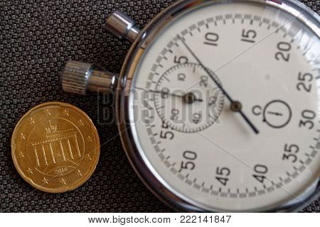 Euro Coin With A Denomination Of 20 Euro Cents (back Side) And Stopwatch On Brown Denim Backdrop - B