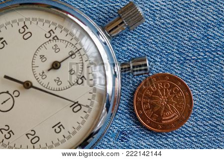 Euro Coin With A Denomination Of 2 Euro Cents (back Side) And Stopwatch On Blue Denim Backdrop - Bus
