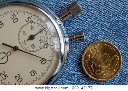 Euro coin with a denomination of twenty euro cents and stopwatch on blue denim backdrop - business background
