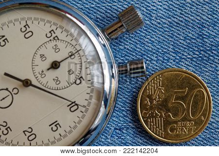 Euro coin with a denomination of fifty euro cents and stopwatch on blue denim backdrop - business background