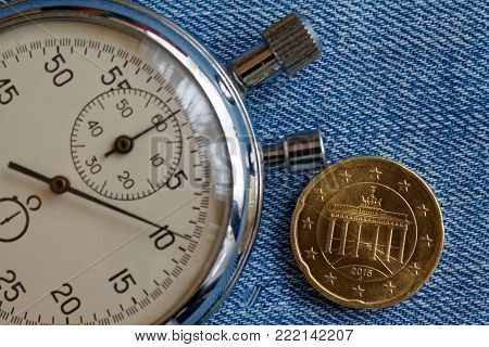 Euro Coin With A Denomination Of 20 Euro Cents (back Side) And Stopwatch On Blue Denim Backdrop - Bu
