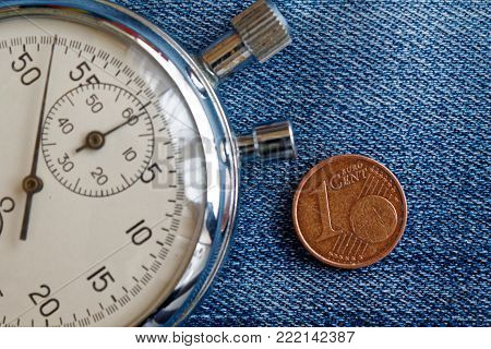 Euro coin with a denomination of one euro cent and stopwatch on worn blue jeans backdrop - business background