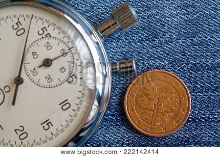 Euro coin with a denomination of 5 euro cents (back side) and stopwatch on worn jeans backdrop - business background