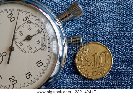 Euro coin with a denomination of ten euro cents and stopwatch on worn blue jeans backdrop - business background