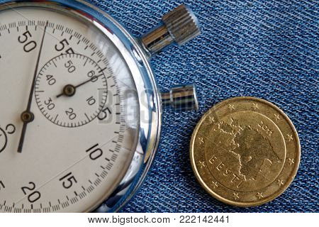 Euro Coin With A Denomination Of 50 Euro Cents (back Side) And Stopwatch On Worn Jeans Backdrop - Bu