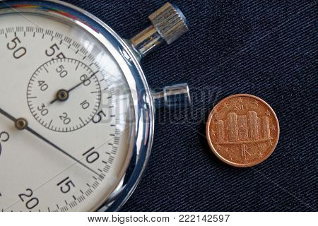 Euro Coin With A Denomination Of One Euro Cent (back Side) And Stopwatch On Worn Black Jeans Backdro