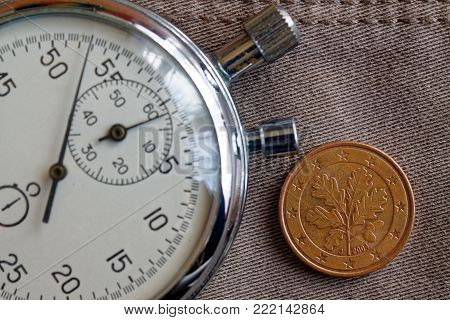 Euro Coin With A Denomination Of 5 Euro Cents (back Side) And Stopwatch On Beige Denim Backdrop - Bu