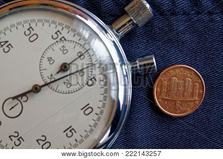 Euro Coin With A Denomination Of 1 Euro Cent (back Side) And Stopwatch On Old Blue Denim Backdrop -