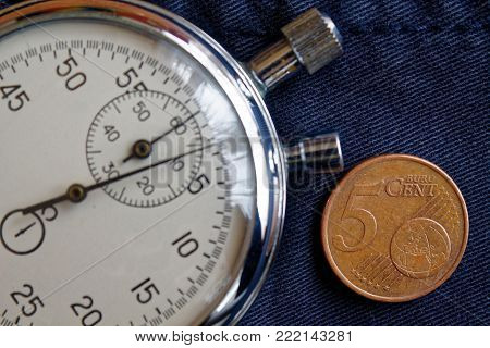 Euro Coin With A Denomination Of Five Euro Cents And Stopwatch On Old Blue Jeans Backdrop - Business