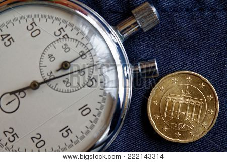Euro Coin With A Denomination Of 20 Euro Cents (back Side) And Stopwatch On Old Blue Denim Backdrop