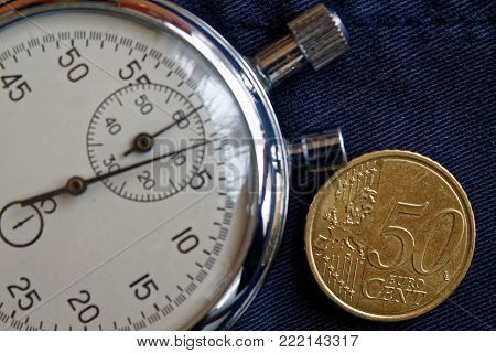 Euro Coin With A Denomination Of Fifity Euro Cents And Stopwatch On Old Blue Jeans Backdrop - Busine