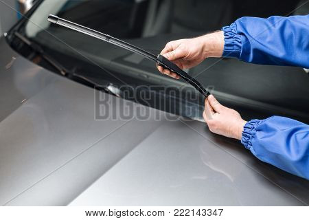 Technician is changing windscreen wipers on a car station