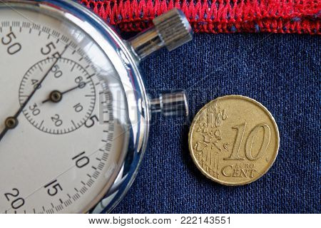 Euro Coin With A Denomination Of Ten Euro Cents And Stopwatch On Worn Blue Denim With Red Stripe Bac
