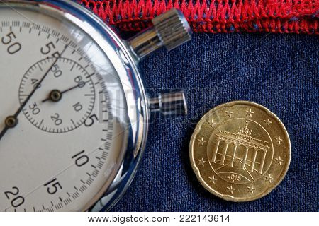 Euro Coin With A Denomination Of 20 Euro Cents (back Side) And Stopwatch On Worn Blue Jeans With Red