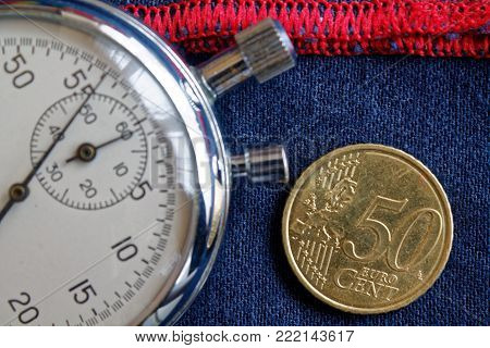 Euro Coin With A Denomination Of Fifty Euro Cents And Stopwatch On Worn Blue Denim With Red Stripe B