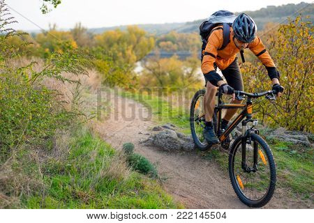 Cyclist in Orange Riding the Mountain Bike on the Autumn Rocky Enduro Trail. Extreme Sport and Enduro Biking Concept.