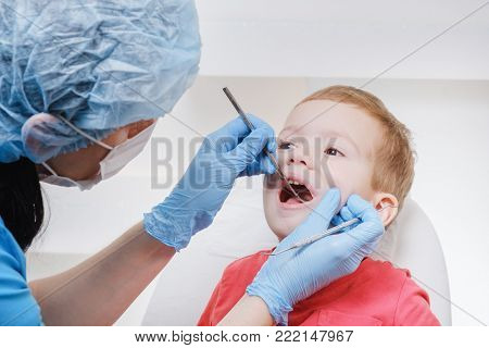 Medical examination of child patient teeth using a mirror of instruments by a dentist. Caries, tooth close up damage, illness.