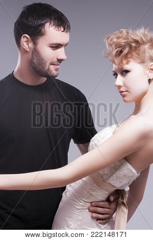 Relationships Concepts. Young Caucasian Couple Posing Together and Emnracing. Female Wearing Tailored Wedding Dress. Against Gray.Vertical Image