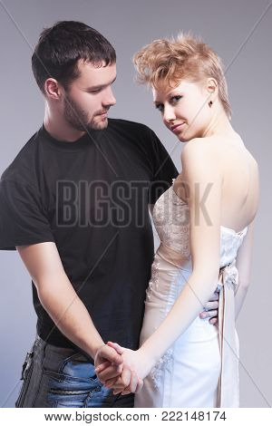 Relationships Concepts. Young Caucasian Couple Posing Together and Emnracing. Female Wearing Tailored Wedding Dress. Against Gray.Vertical Image Composition