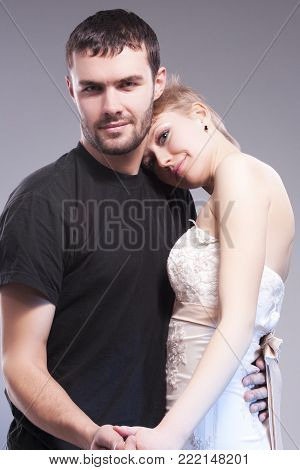 Relationships Ideas and Concepts. Sensual and Positive Caucasian Couple Posing Embraced Together on Gray. Blond Female Wearing Tailored Wedding Dress with Head Over the Man Shoulder. Vertical Composition