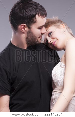 Relationships Ideas and Concepts. Sensual and Positive Caucasian Couple Posing Embraced Together and looking Eye To Eye. Blond Female Wearing Tailored Wedding Dress with Head Over the Man Shoulder. Vertical Composition
