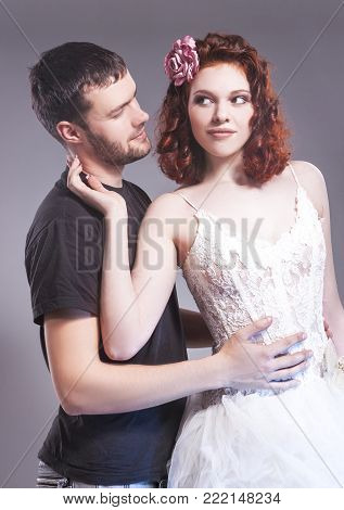 Relationships Ideas. Sensual Caucasian Couple of Posing Embraced Together and Touching Each Other. Smiling Ginger Female Wearing Tailored Wedding Dress. Vertical Composition