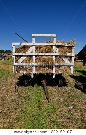 A loaded rack of wheat bundles with a pitch fork sticking out are ready to be fed into the feeder of a threshing machine at a farm show