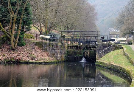 old wooden lock gates on the rochdale canal near hebden bridge with woodland landscape in winter