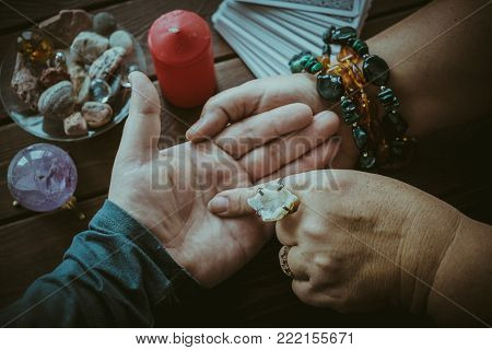 Witch or fortune teller reading fortune lines on male palm or hand, top view, vintage film style toned