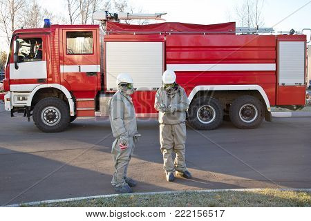 Two men in  chemical protection suite on fire truck background.