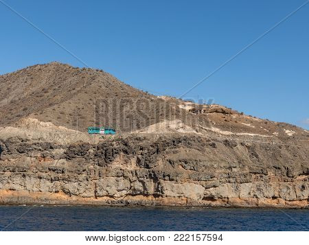 Gran Canaria, Canary Islands in Spain - December 16, 2017: Blue bus driving on the road in the steep mountains at the coast between Puerto de Mogan and Puerto Rico. Layers of volcanic rock. Strata.