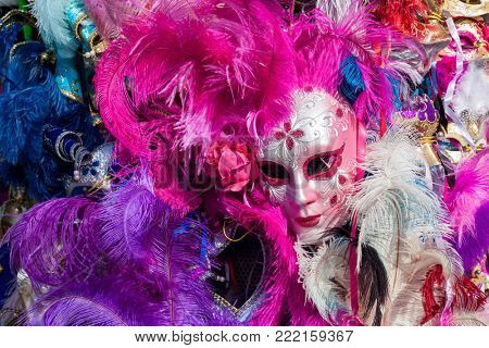 Ornated carnival mask among colorful feathers in Venice, Italy.