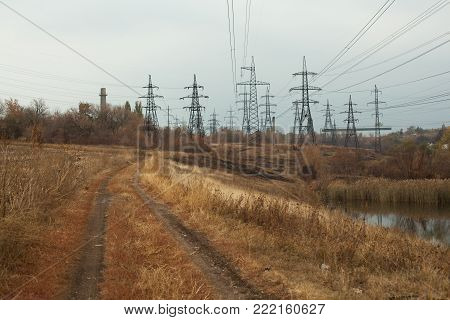 Coal power station in beautiful area full of trees and lake, mirror reflection of energetic pole and power station with chimneys, synergy of industry and nature Horizontal image