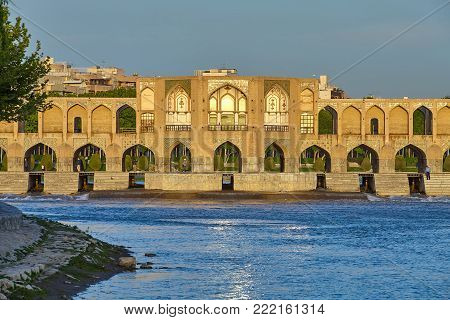 Isfahan, Iran - April 24, 2017: Central Pavilion of Khaju Bridge  over the Zayandeh river in bright sunshine at morning.  Bridge was built in the 17th Century in the Persian Safavid style.