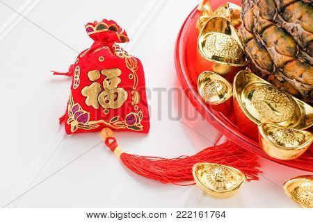 Chinese New year red felt bag ( ang pow ) and pineapple with group of gold ingots in red tray on white wood table.on ingots mean wealthy and on bag mean happiness.pineapple in Chinese mean luck poster