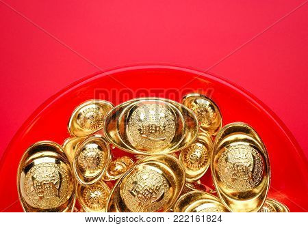 Top view group of golden ingots on red tray at red background.Chinese new year concept,leave space for adding text.Chinese Language on ingot mean wealthy