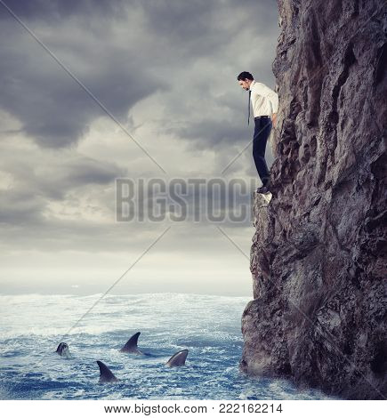 Businessman is likely to fall into the deep sea with shark. Risks and difficulties concept