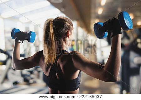 Athletic muscular woman trains biceps with dumbbells at the gym