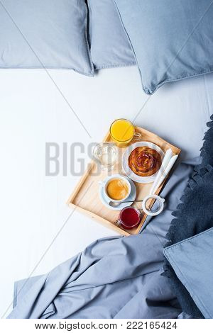Breakfast Bed Wooden Tray Coffee Bun Grey Linens Bedding Sheet Pillow Coverlet Hotel Room Early Morning at Hotel Background Concept Interior