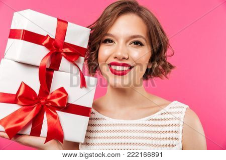 Cose up portrait of a pretty girl dressed in dress holding stack of gift boxes and looking at camera isolated over pink background