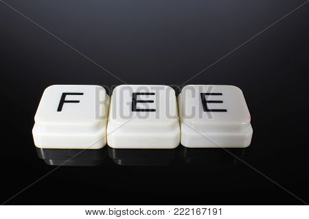 Fee text word title caption label cover backdrop background. Alphabet letter toy blocks on black reflective background. White alphabetical letters. White educational toy block with words on mirror board table.