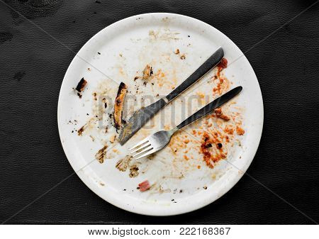 high-angle view of a white ceramic plate with the remains of a pizza, on a black leatherette surface
