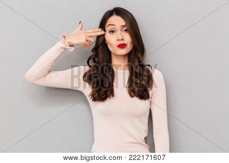 Image of sassy woman with long brown hair emotionally putting fingers to her temple like gun, being naughty over gray wall