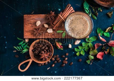 Flat lay with espresso shot with foam on a wooden box, coffee beans, arabica leaves, cinnamon and spices on dark background. Hot drink photography concept.