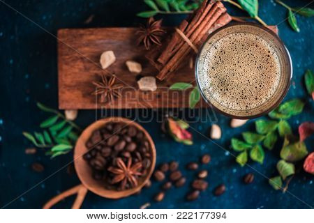 Close-up of espresso shot with foam on a wooden box, coffee beans, arabica leaves, cinnamon and spices on dark background. Hot drink photography concept.