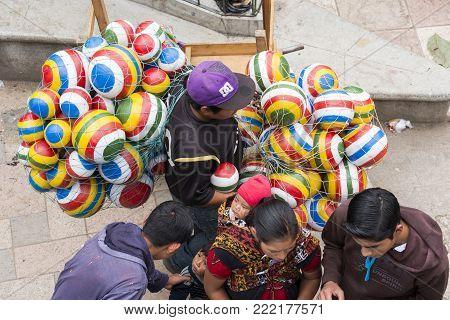 SAN JUAN OSTUNCALCO, GUATEMALA - JUNE 24: Colorful balls carried by an unidentified vendor through crowds at the San Juan Ostuncalco fair in honor of Saint John the Baptist on June 24, 2017 in Guatemala.