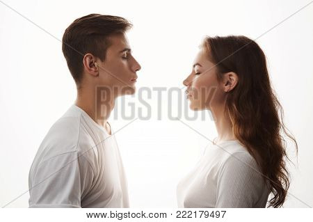 Young woman and man in love standing with closed eyes. Love is in the air, those who jealous, try not to breathe. They do not care about the rest, because in their universe only two of them exist. Copy space.