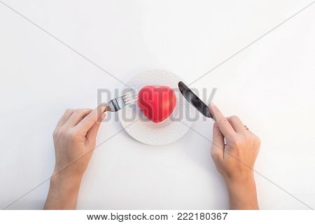 composition on a white background of the plates, heart-shaped, hands with fork and knife