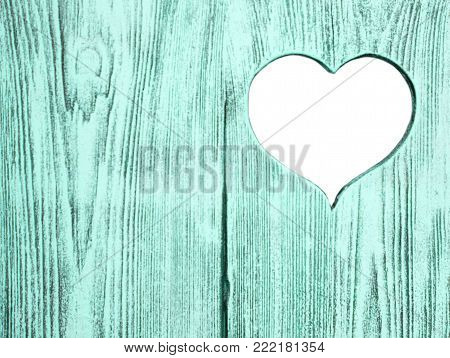 White heart carved in a blue wooden board. Background