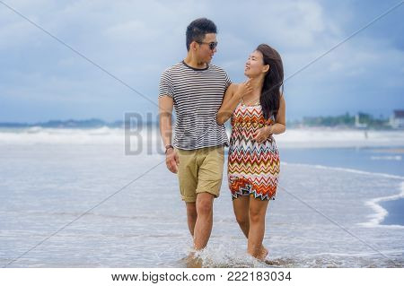 young beautiful and Asian Chinese romantic couple walking together embracing on the beach happy in love enjoying holidays and relax smiling joyful in tourism trip and romance concept